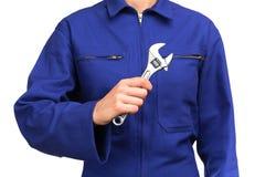 Γυναίκα στην μπλε ομοιόμορφη εκμετάλλευση εργασίας ένα γαλλικό κλειδί πιθήκων Στοκ φωτογραφία με δικαίωμα ελεύθερης χρήσης