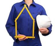 Γυναίκα στην μπλε ομοιόμορφη εκμετάλλευση εργασίας ένα χρονόμετρο με διακόπτη και ένα κράνος Στοκ Εικόνες