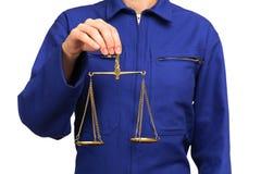 Γυναίκα στην μπλε ομοιόμορφη εκμετάλλευση εργασίας μια κλίμακα της δικαιοσύνης Στοκ Εικόνα