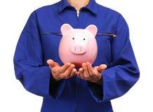 Γυναίκα στην μπλε ομοιόμορφη εκμετάλλευση εργασίας μια piggy τράπεζα Στοκ Εικόνες