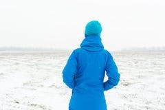 Γυναίκα στην μπλε στάση σε έναν χιονώδη τομέα Στοκ φωτογραφία με δικαίωμα ελεύθερης χρήσης