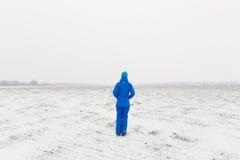 Γυναίκα στην μπλε στάση σε έναν χιονώδη τομέα Στοκ Φωτογραφία