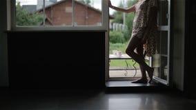 Γυναίκα στην ξυπόλυτη στάση πυτζαμών νύχτας στη ανοιχτή πόρτα μπαλκονιών φιλμ μικρού μήκους