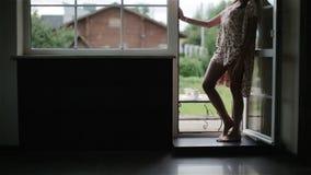 Γυναίκα στην ξυπόλυτη στάση πυτζαμών νύχτας στις ανοιχτές πόρτες μπαλκονιών απόθεμα βίντεο