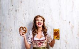 Γυναίκα στην παραδοσιακά βαυαρικά μπύρα και pretzel εκμετάλλευσης φορεμάτων στοκ εικόνες με δικαίωμα ελεύθερης χρήσης