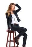 Γυναίκα στην τοποθέτηση σακακιών δέρματος στο υπόβαθρο στούντιο ενώ arrang Στοκ φωτογραφία με δικαίωμα ελεύθερης χρήσης