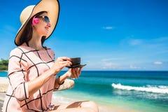 Γυναίκα στην τροπική παραλία με το φλυτζάνι καφέ που έχει το πρόγευμα Στοκ φωτογραφία με δικαίωμα ελεύθερης χρήσης