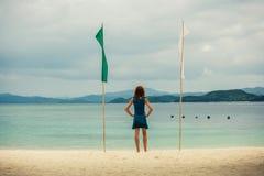 Γυναίκα στην τροπική παραλία με τις σημαίες Στοκ Εικόνα