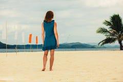Γυναίκα στην τροπική παραλία με τις σημαίες Στοκ Εικόνες