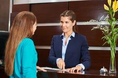 Γυναίκα στην υποδοχή ξενοδοχείων που προσφέρει τις συμβουλές Στοκ Φωτογραφίες