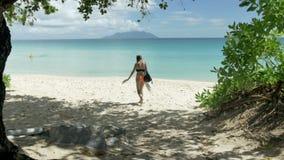 Γυναίκα στην όμορφη παραλία στις Σεϋχέλλες που περπατούν στην άμμο, οπισθοσκόπο απόθεμα βίντεο