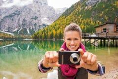 Γυναίκα στη λίμνη Bries που στοχεύει τη κάμερα πίσω στο θεατή στοκ φωτογραφίες