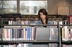 Γυναίκα στη βιβλιοθήκη στοκ εικόνα με δικαίωμα ελεύθερης χρήσης