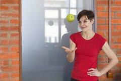 Γυναίκα στη γυμναστική με τη Apple, Στοκ Φωτογραφία