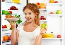 Γυναίκα στη διατροφή που επιλέγει μεταξύ των υγιών και ανθυγειινών τροφίμων πλησίον στοκ εικόνα με δικαίωμα ελεύθερης χρήσης