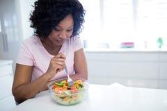 Γυναίκα στη διατροφή που τρώει τη σαλάτα στην κουζίνα Στοκ εικόνες με δικαίωμα ελεύθερης χρήσης