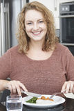 Γυναίκα στη διατροφή που τρώει το υγιές γεύμα στην κουζίνα Στοκ Εικόνες