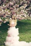 Γυναίκα στη ρόδινη κοντινή άνθιση φορεμάτων στοκ εικόνες