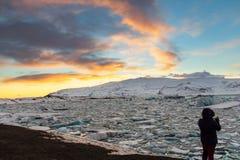 Γυναίκα στη σκιαγραφία που φωτογραφίζει τη λιμνοθάλασσα παγετώνων στην Ισλανδία στοκ φωτογραφίες