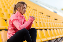 Γυναίκα στη συνεδρίαση αθλητικής ένδυσης στην καρέκλα στο στάδιο Στοκ εικόνες με δικαίωμα ελεύθερης χρήσης