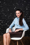 Γυναίκα στη συνεδρίαση επιχειρησιακού ιματισμού στην έδρα και το χαμόγελο στοκ φωτογραφίες