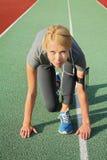 Γυναίκα στη χαμηλή θέση έναρξης στο στάδιο Αθλητής στην αρχική θέση Θηλυκός δρομέας που ακούει τη μουσική mp3 στο φορέα ή το κινη Στοκ Εικόνες