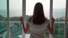 Γυναίκα στις άσπρες πόρτες και το κοίταγμα μπαλκονιών μπλουζών ανοίγοντας έξω Απολαμβάνοντας τη θέα θάλασσας έξω απόθεμα βίντεο