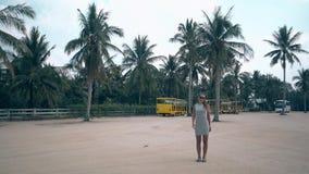Γυναίκα στις γκρίζες στάσεις φορεμάτων και γυαλιών ηλίου στο ευρύ τετράγωνο απόθεμα βίντεο