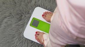 Γυναίκα στις ηλεκτρονικές κλίμακες με τη σύλληψη διατροφής απόθεμα βίντεο