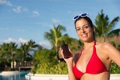 Γυναίκα στις θερινές διακοπές που κρατούν το suntan μπουκάλι λοσιόν Στοκ Φωτογραφία