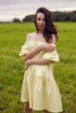 Γυναίκα στις κίτρινες στάσεις φορεμάτων σε έναν τομέα Στοκ εικόνες με δικαίωμα ελεύθερης χρήσης