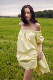 Γυναίκα στις κίτρινες στάσεις φορεμάτων σε έναν τομέα Στοκ Φωτογραφία