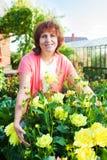 Γυναίκα στις προσοχές κήπων για τα λουλούδια Στοκ Φωτογραφίες