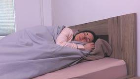 Γυναίκα στις πυτζάμες στο κρεβάτι απόθεμα βίντεο