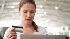 Γυναίκα στον αερολιμένα που ψωνίζει on-line με την πιστωτική κάρτα στο lap-top περιμένοντας την αναχώρηση πτήσης φιλμ μικρού μήκους