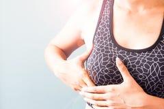 Γυναίκα στον αθλητικό στηθόδεσμο που κρατά το στήθος της, καρκίνος του μαστού Στοκ Εικόνες
