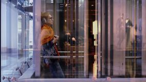 Γυναίκα στον ανελκυστήρα με ένα φλιτζάνι του καφέ, που κινείται κάτω απόθεμα βίντεο