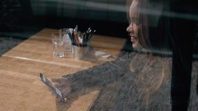 Γυναίκα στον καθιερώνοντες τη μόδα καφέ κατανάλωσης καφέδων και το τηλέφωνο χρήσης Νέο όμορφο καυκάσιο πρότυπο Αντανακλάσεις από  απόθεμα βίντεο