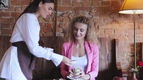 Γυναίκα στον καφέ κατανάλωσης καφέδων με τις καραμέλες σοκολάτας απόθεμα βίντεο