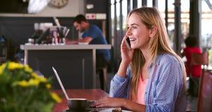 Γυναίκα στον καφέ που λειτουργεί στο lap-top και που απαντά στο τηλέφωνο απόθεμα βίντεο