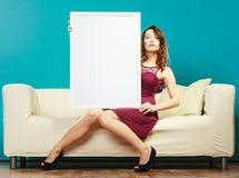 Γυναίκα στον κενό πίνακα παρουσίασης εκμετάλλευσης καναπέδων Στοκ Εικόνα