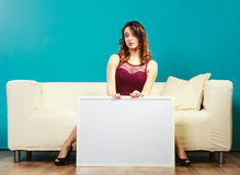 Γυναίκα στον κενό πίνακα παρουσίασης εκμετάλλευσης καναπέδων Στοκ εικόνα με δικαίωμα ελεύθερης χρήσης