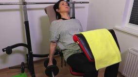 Γυναίκα στον πάγκο γυμναστικής που χρησιμοποιεί τους αλτήρες φιλμ μικρού μήκους