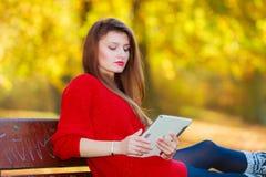Γυναίκα στον πάγκο στο πάρκο με την ταμπλέτα Στοκ Φωτογραφίες