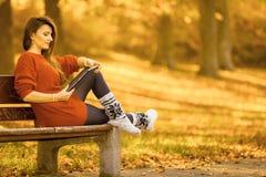 Γυναίκα στον πάγκο στο πάρκο με την ταμπλέτα Στοκ Εικόνα