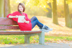Γυναίκα στον πάγκο στο πάρκο με την ταμπλέτα Στοκ εικόνες με δικαίωμα ελεύθερης χρήσης