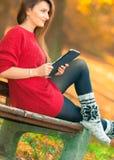 Γυναίκα στον πάγκο στο πάρκο με την ταμπλέτα Στοκ φωτογραφία με δικαίωμα ελεύθερης χρήσης
