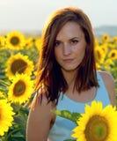 Γυναίκα στον τομέα ηλίανθων στο χρόνο ηλιοβασιλέματος Στοκ Φωτογραφίες