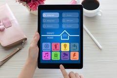 Γυναίκα στον υπολογιστή ταμπλετών επιτραπέζιας εκμετάλλευσης με app το έξυπνο σπίτι Στοκ εικόνες με δικαίωμα ελεύθερης χρήσης