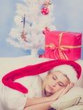 Γυναίκα στον ύπνο καπέλων Santa στον καναπέ Στοκ φωτογραφία με δικαίωμα ελεύθερης χρήσης